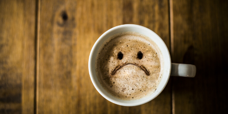 Frowning face in a cup of coffee