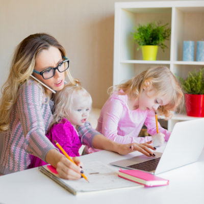 Woman Working at Home with Kids around her