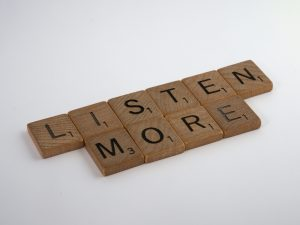 wooden tiles with a message listen more